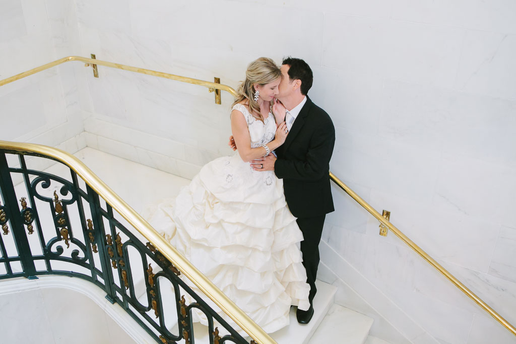Groom kisses his bride on the stairs