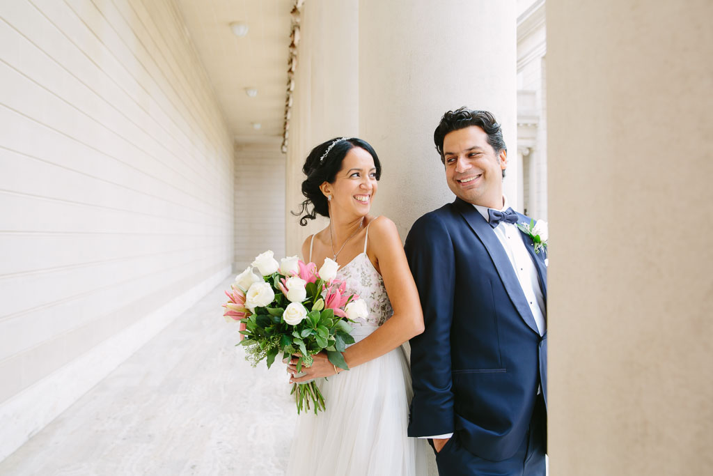 Bride and groom at the Legion of Honor after their City Hall wedding. pink and white bridal bouquet. Navy blue tuxedo for groom.