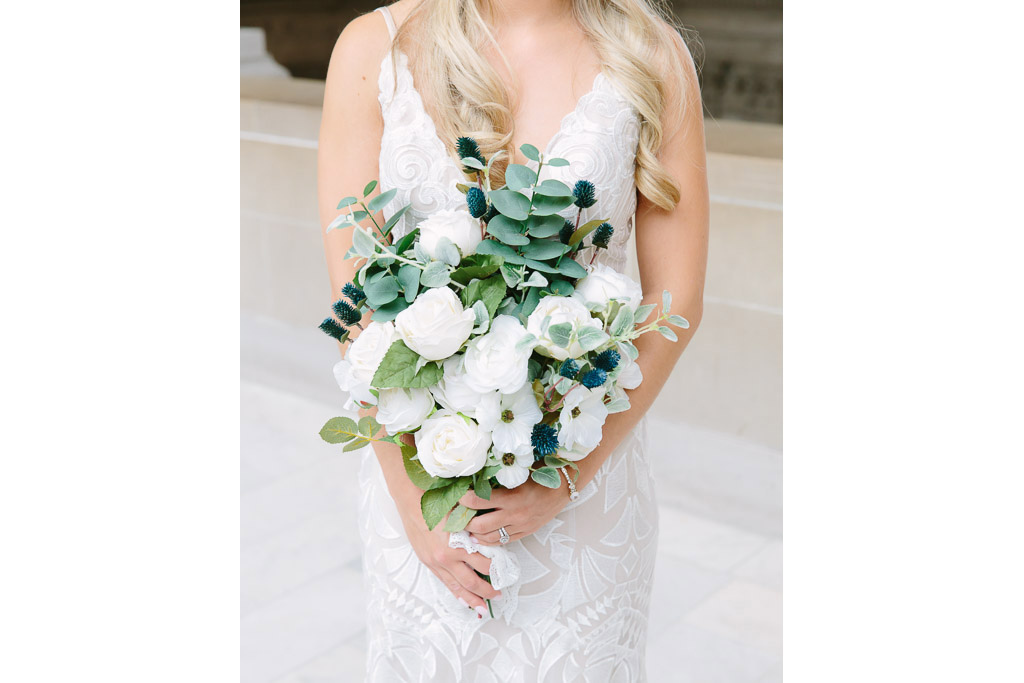 Bride holding a white and green bridal bouquet floral arrangement