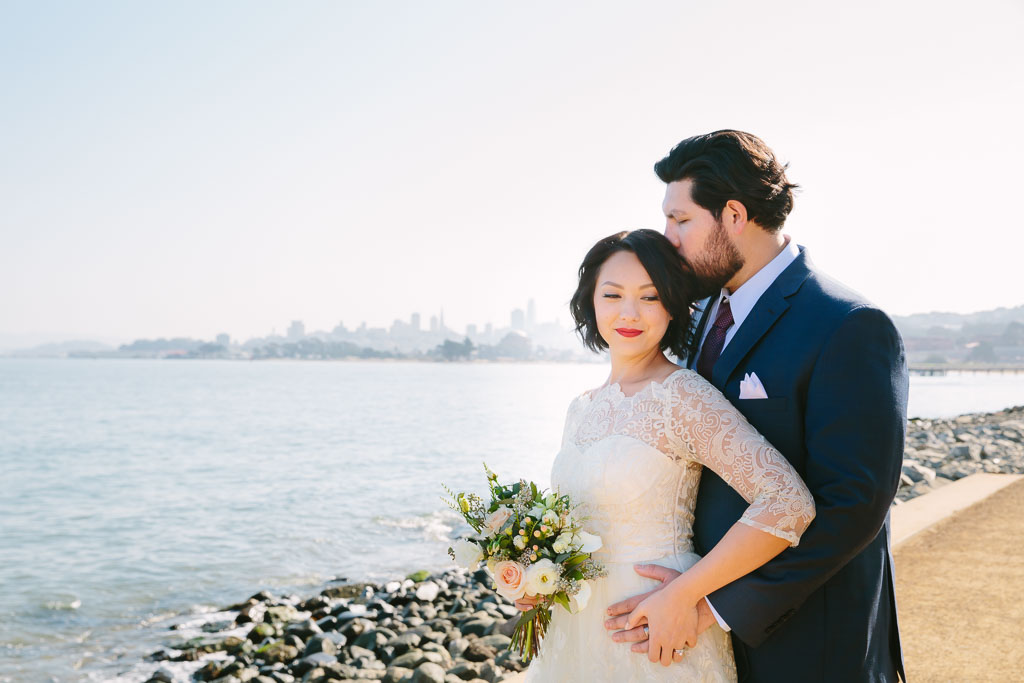 Groom kisses his bride with a view of the San Francisco skyline behind them