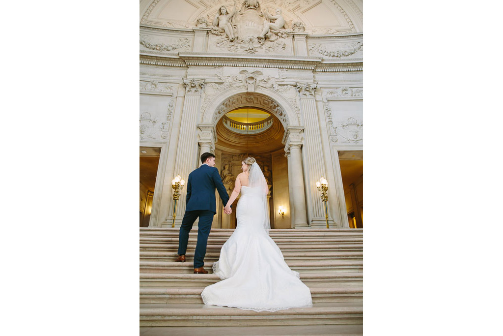 Bride and groom stand on staircase. Bride is wearing a mermaid style dress with a long train cascading down the stairs.