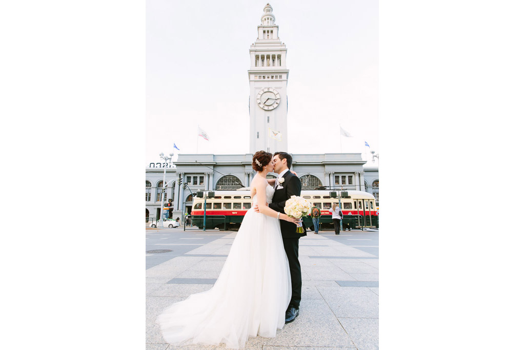 Bride and groom kissing in front of the Ferry Building in San Francisco with a trolley in the background