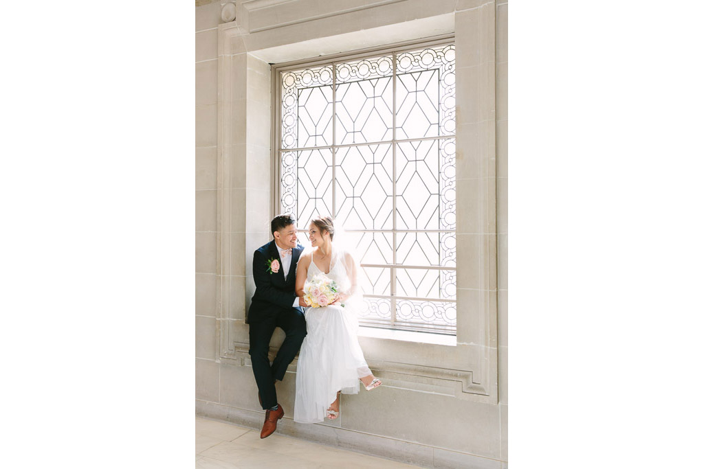 Bride and groom sitting on window sill