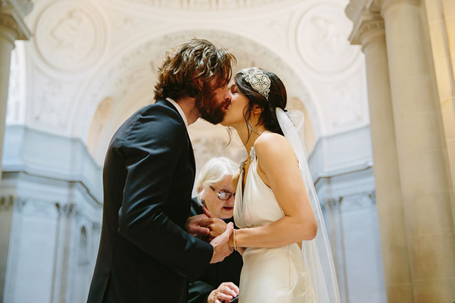 Bride and groom kiss during their wedding ceremony at San Francisco City Hall