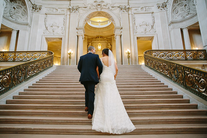 Bride and groom walking up the stairs of the Grand Staircase inside San Francisco City Hall