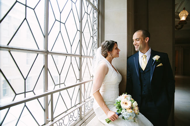 Bride sitting in window looking at her groom inside San Francisco City Hall