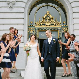Bride and groom walking down the stairs of San Francisco City Hall with their family clapping and standing around them