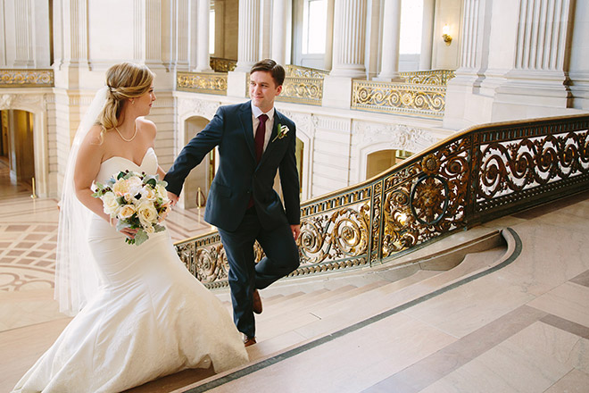 Bride and groom walking and holding hands on the Grand Staircase
