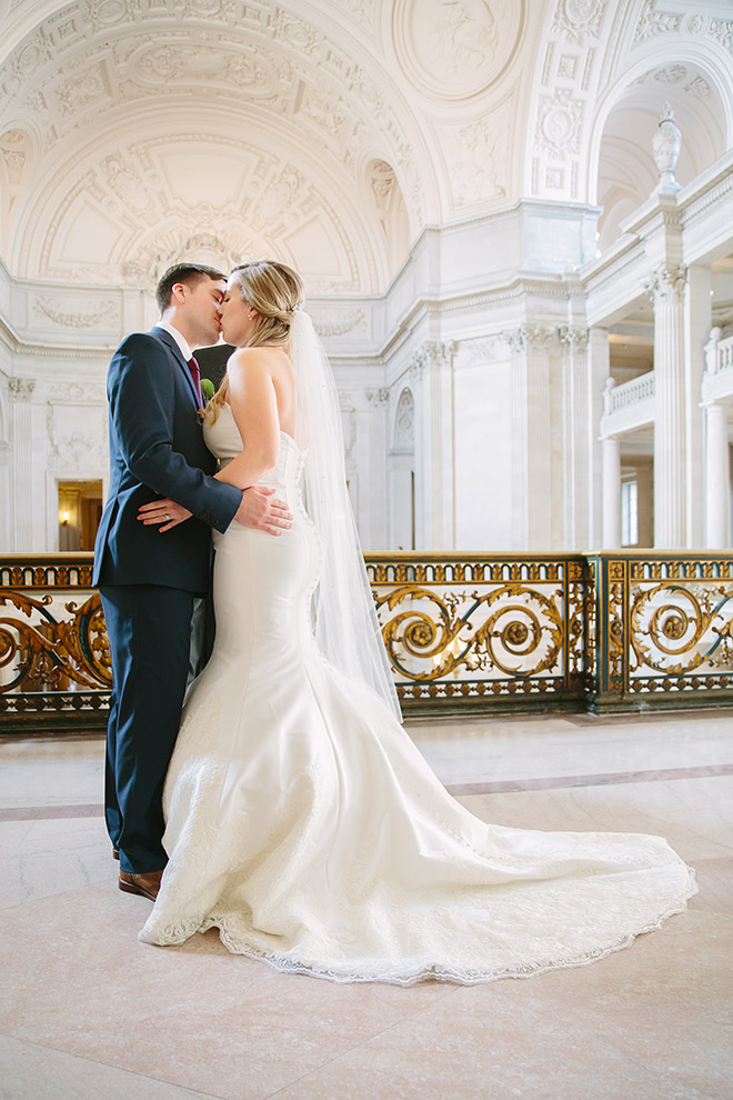 Bride and groom kiss during their wedding ceremony on the Mayor's Balcony