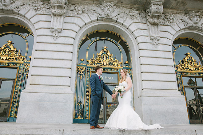 Bride and groom holding hands at the front entrance of San Francisco City Hall