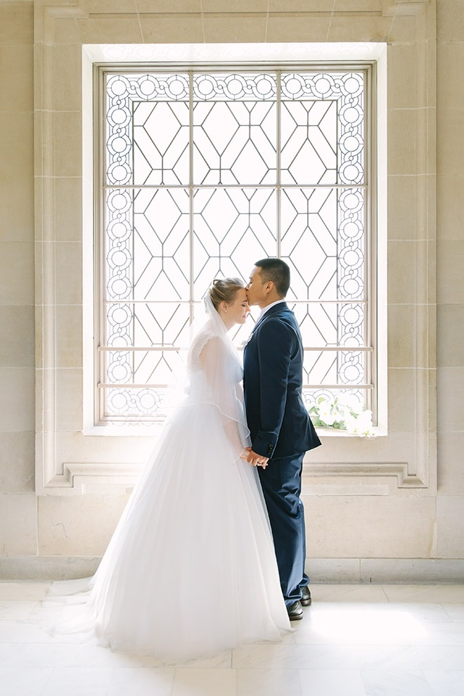 Groom kisses his bride on her forehead. They are standing on the Third Floor of San Francisco City Hall. wedding photographer Lilia Photography