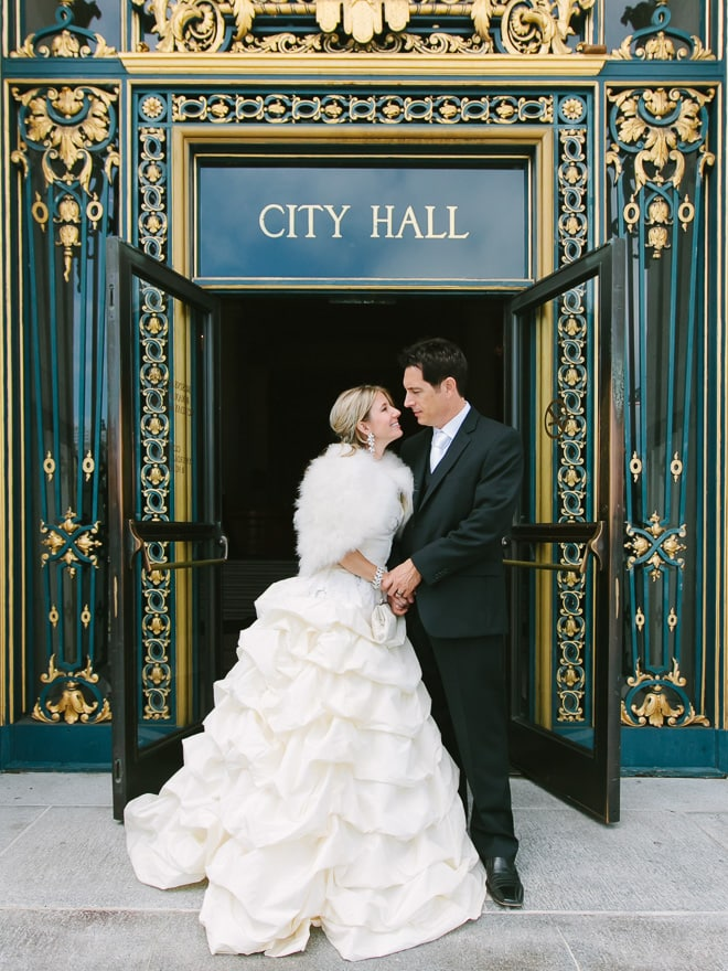 Bride and groom standing at the front door of San Francisco City Hall wedding