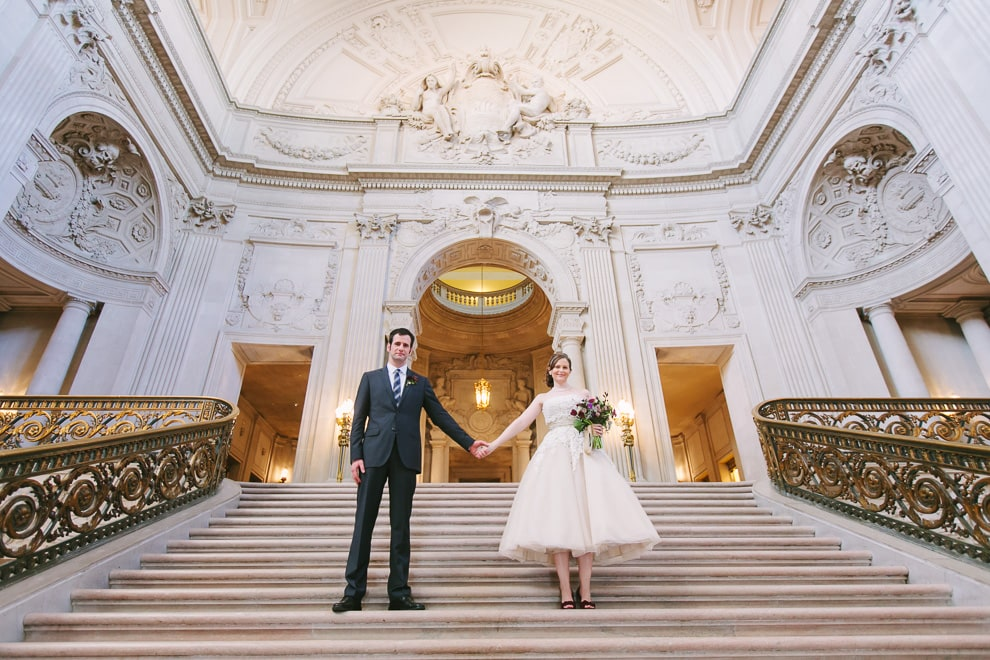 Bride and Groom at their San Francisco City Hall wedding standing on the Grand Staircase