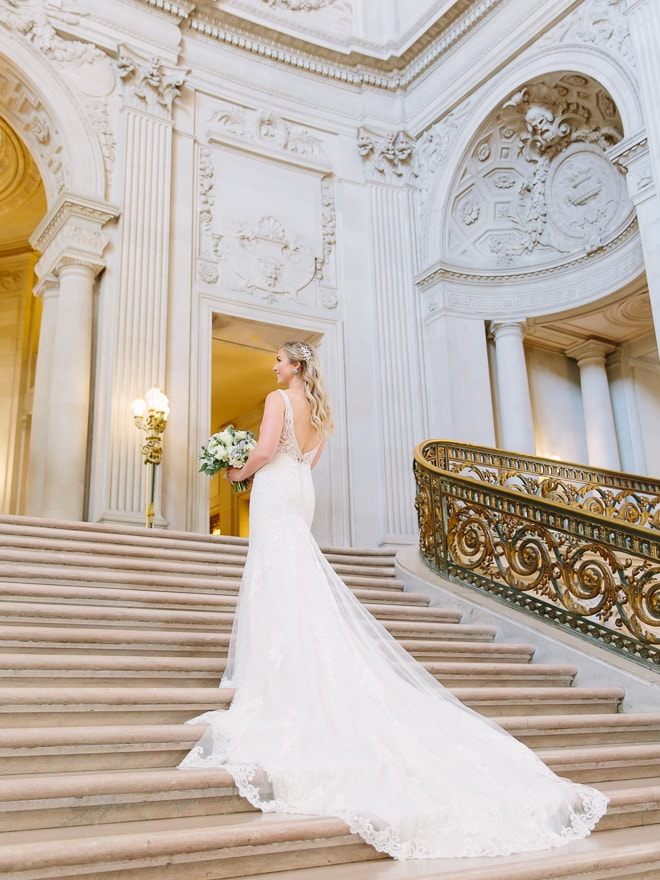 Bride at her San Francisco City Hall wedding standing on the Grand Staircase