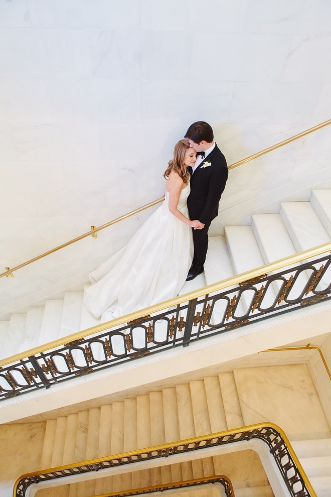 Bride and groom standing on the staircase at their San Francisco City Hall wedding
