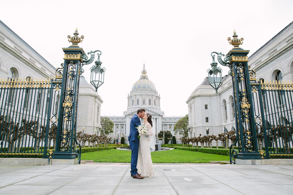 Bride and groom standing in front of San Francisco City Hall in Veterans Memorial Park