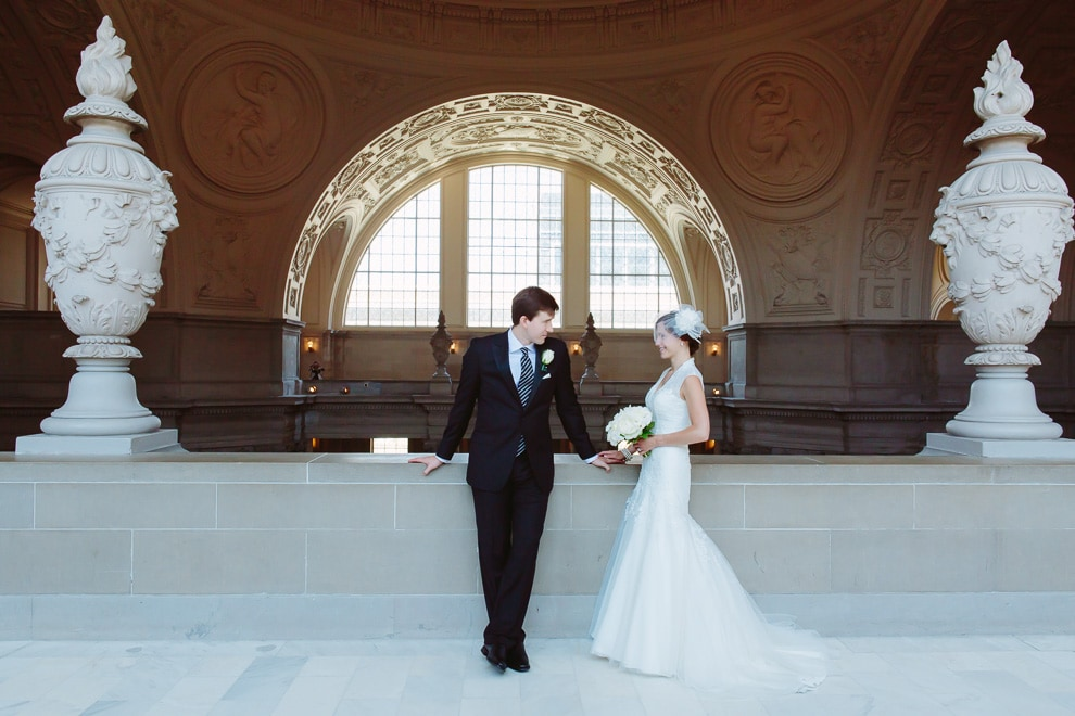 San Francisco City Hall wedding photo. Bride and groom standing on the Fourth Floor North Gallery.