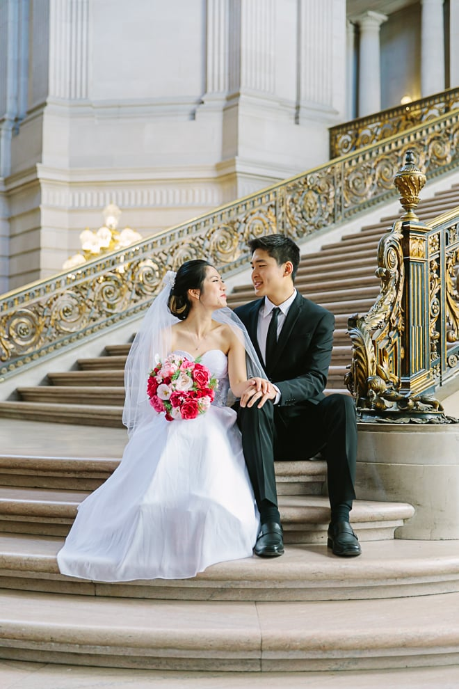 San Francisco City Hall wedding. How to get married at City Hall. Bride and groom sitting together on the Grand Staircase.