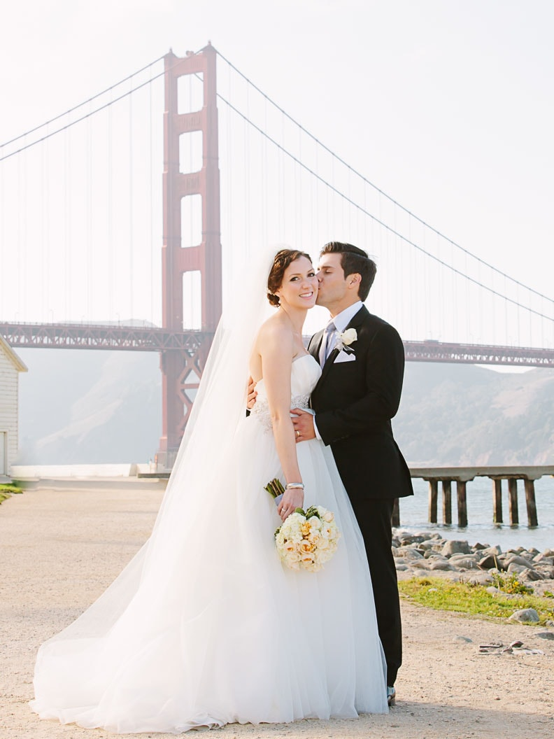 San Francisco Wedding Photographer. Bride and groom standing in front of the Golden Gate Bridge in San Francisco.