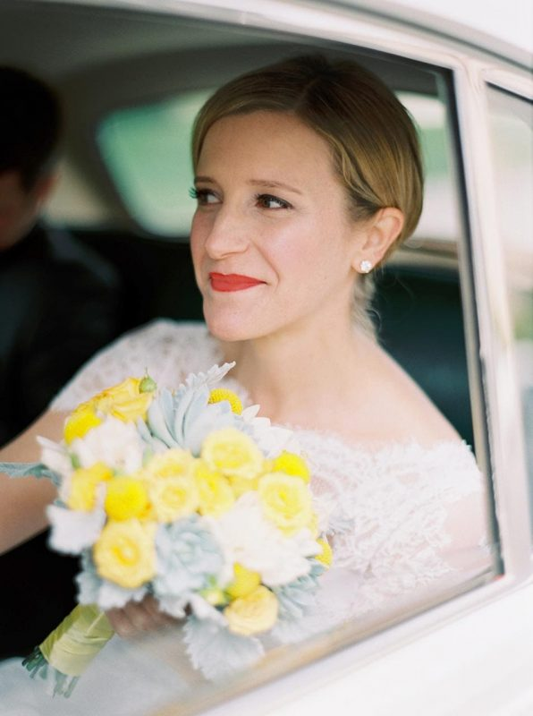 Bride looking out the window of a car. She is holding a bridal bouquet with white and yellow flowers.