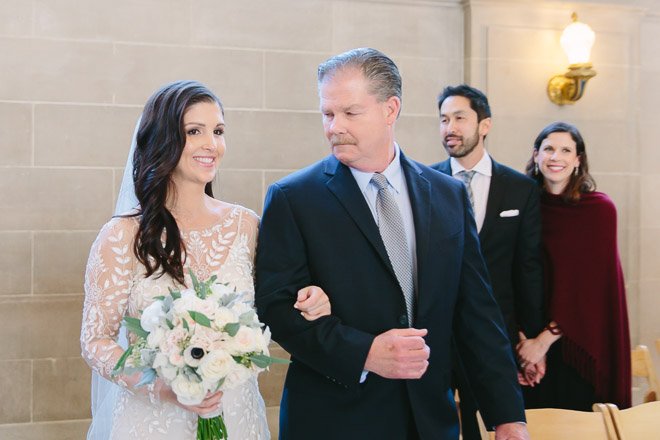 Bride walks down the aisle with her father during her San Francisco City Hall wedding ceremony