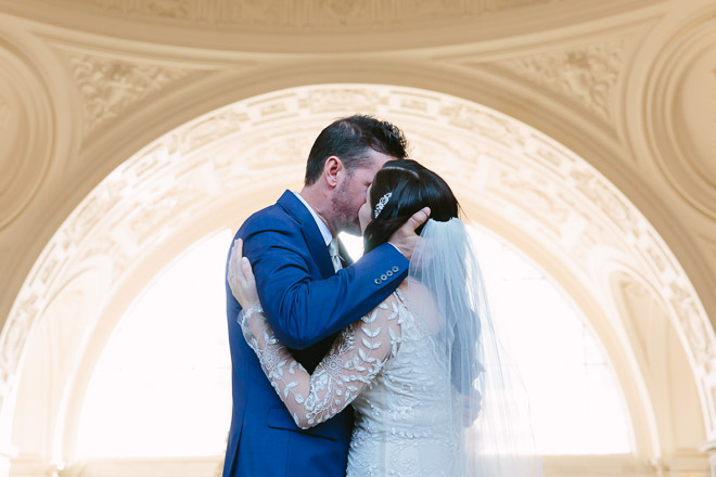 Groom kisses his bride during their wedding ceremony on the Fourth Floor North Gallery inside San Francisco City Hall