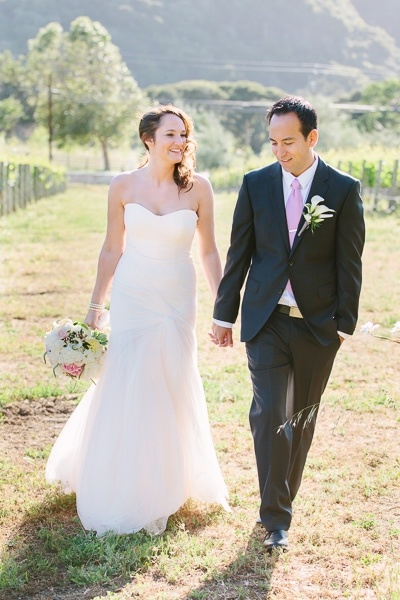 Bride and groom walking and holding hands in a vineyard at their Bernardus Lodge Carmel Valley wedding