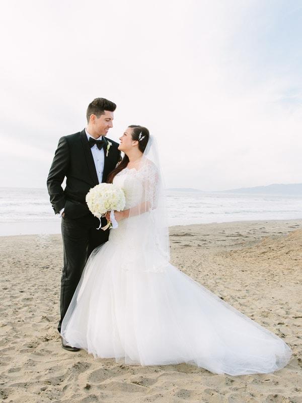 Bride and groom standing on a San Francisco beach. San Francisco wedding photographer.