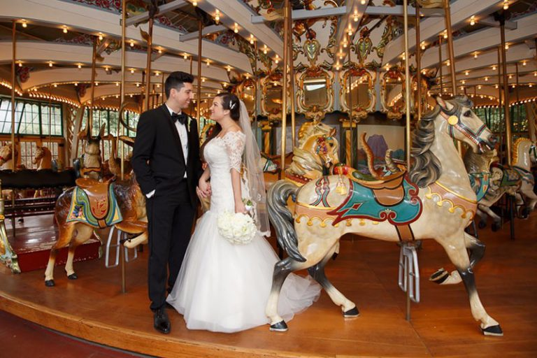 San Francisco Zoo wedding. Bride and groom looking at each other. They are standing on the carousel during their wedding reception.