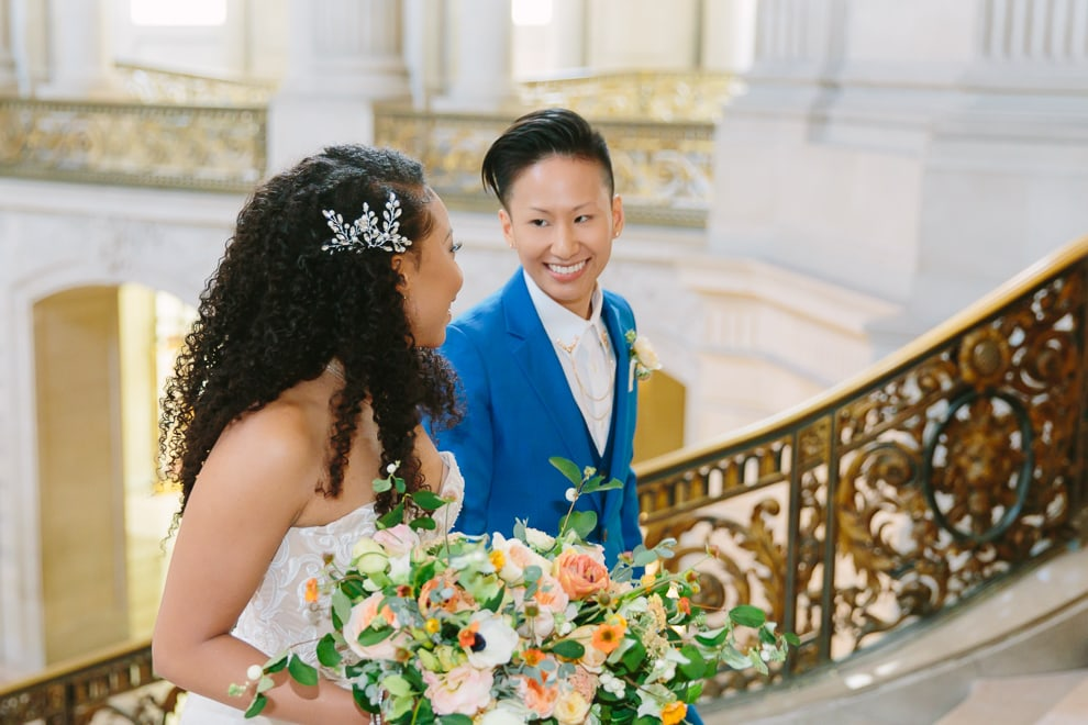 Two brides walking up the Grand Staircase inside San Francisco City Hall