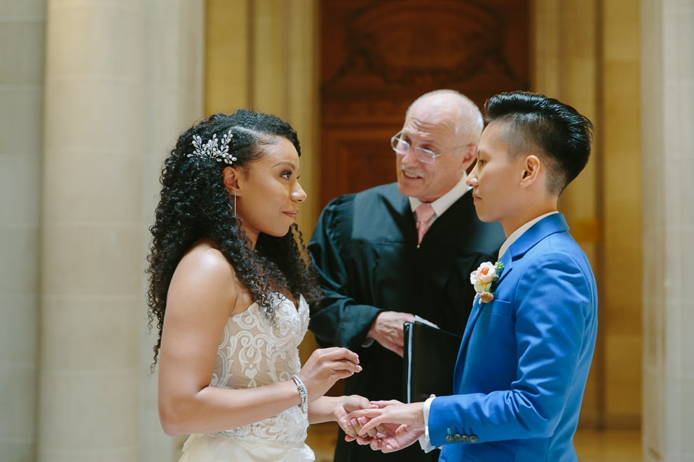 One bride places a wedding ring on her bride at their San Francisco City Hall wedding
