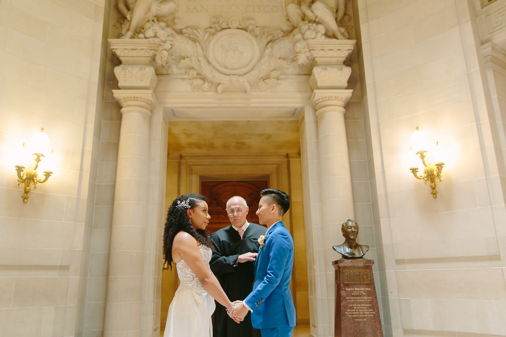Two brides holding hands during their wedding ceremony at San Francisco City Hall