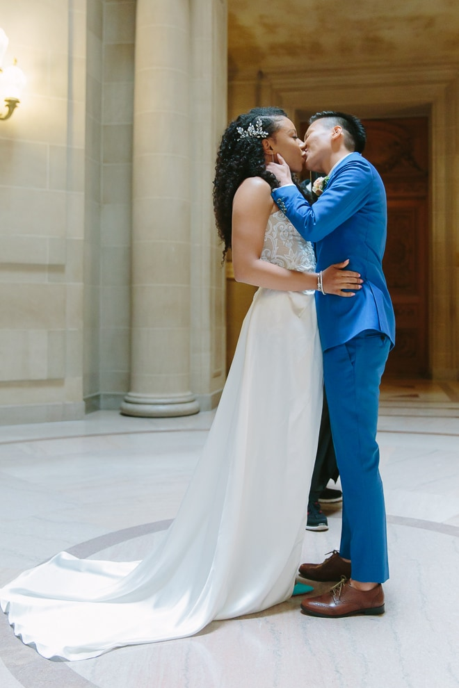 Two brides kiss during their wedding ceremony at San Francisco City Hall