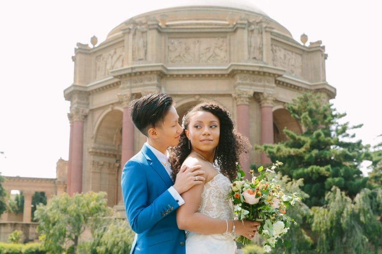 Two brides standing in front of the Palace of Fine Arts in San Francisco