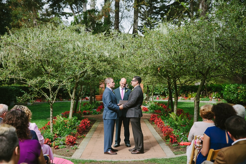 Two grooms holding hands during their wedding ceremony at Shakespeares Garden in Golden Gate Park. San Francisco wedding venue.