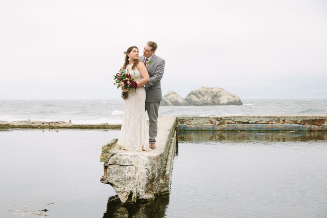 Best engagement session locations in San Francisco. Sutro Baths. Bride and groom holding each other, standing in front of the Sutro Baths.