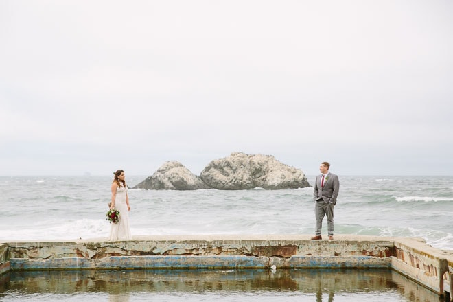 Best engagement session locations in San Francisco. Bride and groom standing on wall at the Sutro Baths. View of the Pacific Ocean behind them