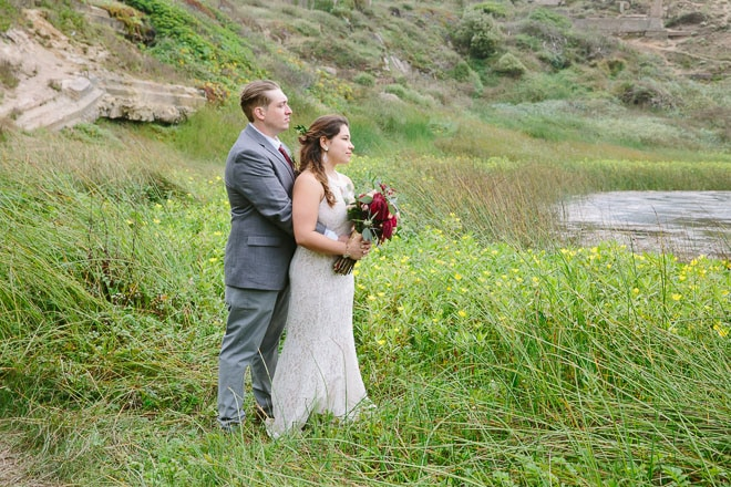 Top engagement session photo locations in San Francisco. Bride and groom holding each other, standing in tall grass at the Sutro Baths near Lands End.